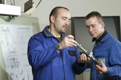 Mitarbeiter der Produktion der Zuther GmbH mit einer Ersatzteil für eine Maschine