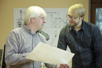 Zwei Mitarbeiter der Zuther GmbH bei der Planung einer neuen Anlage mit Grundrissen