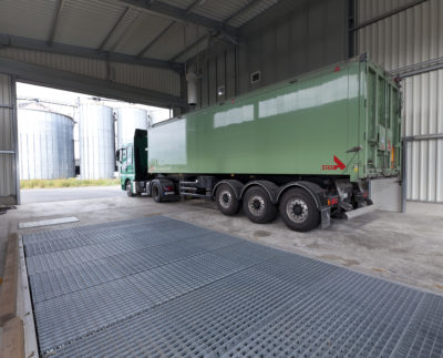 A truck stops at a grain collector to unload grain on a silo system