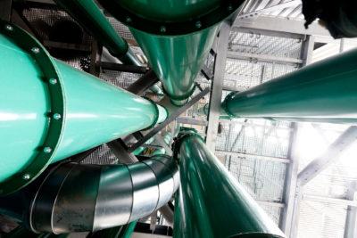 Mehrere, grüne Gurtelevatoren von Zuther in einem Maschinenhaus mit weiterer Fördertechnik