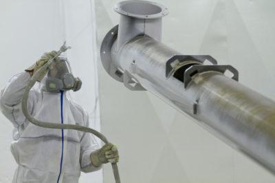 Mitarbeiter bei der Lackierung einer Rohranlage nach MetallbearbeitungZuther GmbH